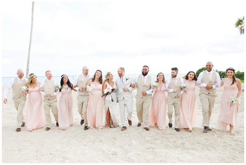 Bridal party walking beach photo